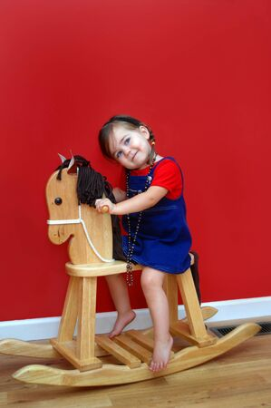 Little girl rides her wooden rocking horse and dreams of one day having a real horse.  Walls are deep red and little girl is wearing a red shirt and denim overall.  Her eyes are skyward as if asking for a horse.