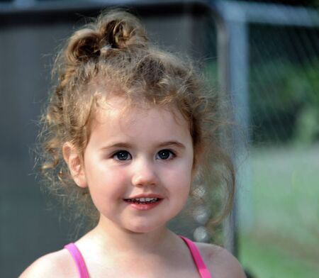 Curls surround little girls head.  Closeup shows the cute twinkle in her eyes.  Pink straps on her shoulders.