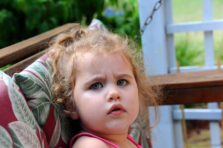 Frown lines perch on a sweet faced little girl.  she is crabby and grouchy as she sits on her front porch swing.  She has curly hair and a ponytail.