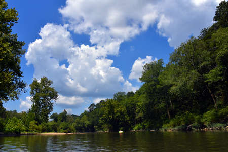 Woman floats lazily down the Caddo River in Glenwood, Arkansas. She is surrounded by Arkansas nature.