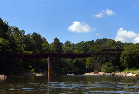Group of people float the Caddo River at Glenwood, Arkansas. They are nearing the Glenwood Railroad Bridge.