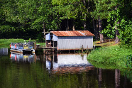 Rough party barge is tied up to small dock. Tin building serves as boat house and storage. All sit on White Oak Lake in South Arkansas.