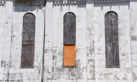 Three arched windows are closed off with plywood on the Brick Church in Memphis, Tennessee.  Historic church is also called Chelsea Avenue Presbyterian Church.