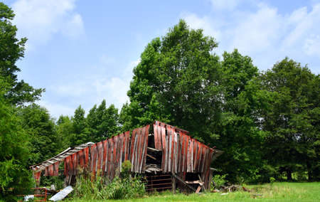 Arkansas, red, wooden barn is derelict and ruined. Its' boards are broken and warped and roof is gone.