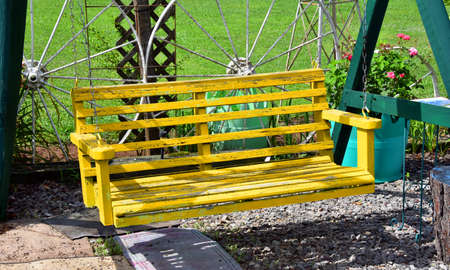 Yellow wooden swing is suspended by chains hooked to green wooden poles. Yellow paint is cracked and weathered. Banque d'images