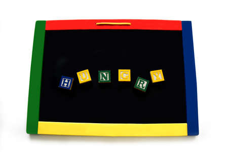 Wooden block letters spell the word hungry on a magnetic board.  Image could represent childhood hunger.  Board is rimmed with primary colors. 스톡 콘텐츠