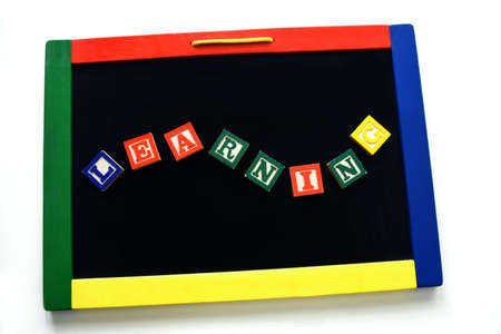 Magnetic block letters spell the word learning.  They cling to a magnetic board rimmed by primary colors.