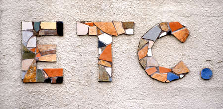 The word et cetera is formed from grouping broken tile into the letters ETC. The background is textured concrete.