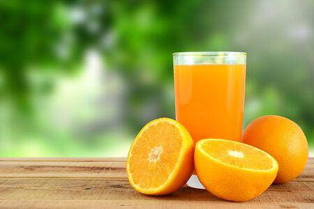 Orange juice and oranges on wooden table. Stockfoto