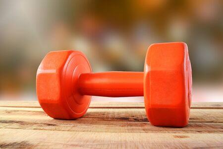Orange dumbbell on wooden. Stock fotó