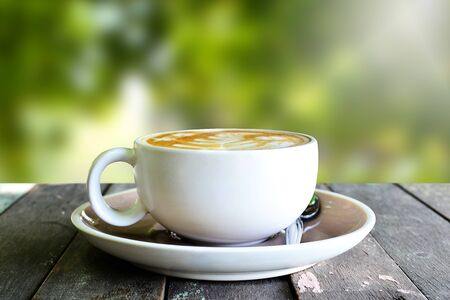 Coffee cup on wooden table and blur background.