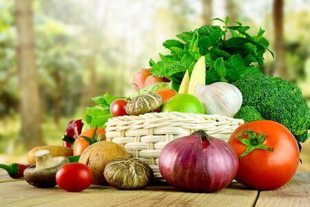 Frisches Gemüse auf Holz- und unscharfem Gartenhintergrund. Standard-Bild