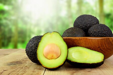 Avocado on wooden table and blurred garden background.