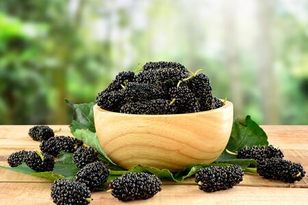 Mulberries on wooden table and blurred nature background. Stockfoto