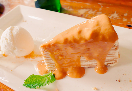 A peice of Thai tea crepe cake served with a scoop of vanilla ice cream garnihed with mint leaf Stock Photo