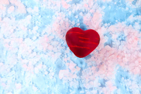 Red heart with wounds on pink-blue ice. Anti Valentine. Shows pain, fire, broken feelings. Copy space