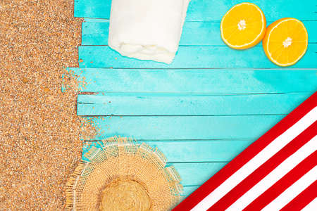 Beach layout. Pebbled sand with an azure horizontal wooden pier or sun lounger. Straw hat, towel and yellow oranges. Travel and tourism. Copy space