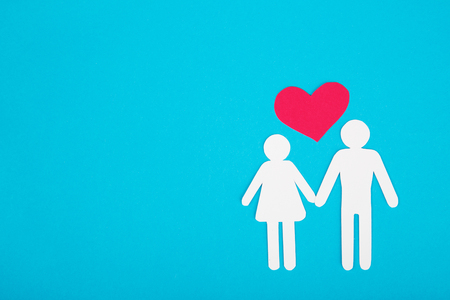 linked hands: Cardboard figures of two peoples on a blue background. The symbol of unity and happiness.