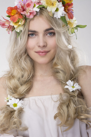 Beauty Fashion Portrait. Beautiful Woman with Curly Hair, Makeup and Flowers Wreath Stock Photo