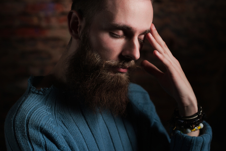 sullen: young handsome bearded hipster man in studio