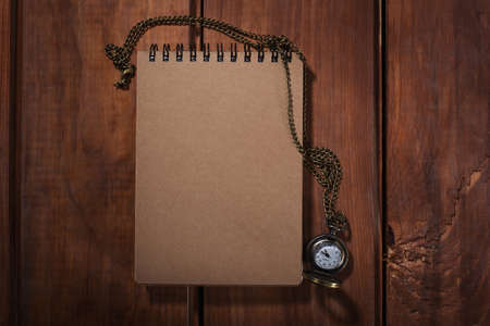 desperado: Old notebook with watches on the wood background