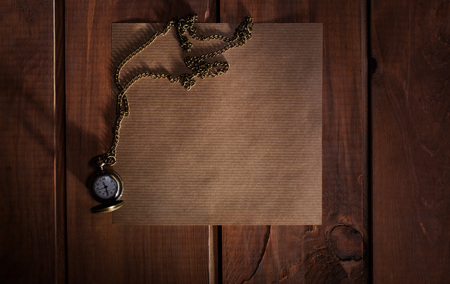 desperado: Old paper on the wood background with watch