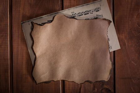 desperado: Old paper and a blanc with musical notes on wooden background Stock Photo