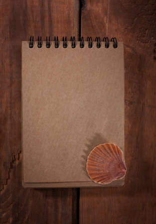 old notebook: Old notebook with shell on wooden background