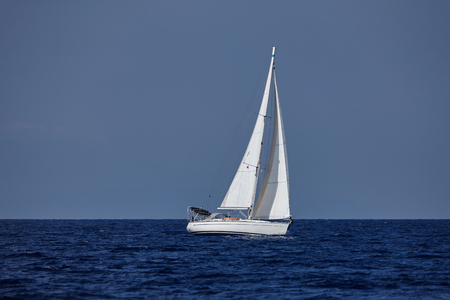 sailing boats: The white sails of yachts on the background of sea and sky