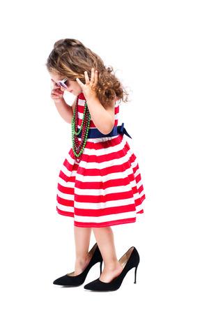 女の子は、白い背景で隔離の大きなかかとの高い母親の靴を履いて