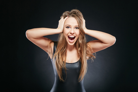 portrait of surprised woman over dark background