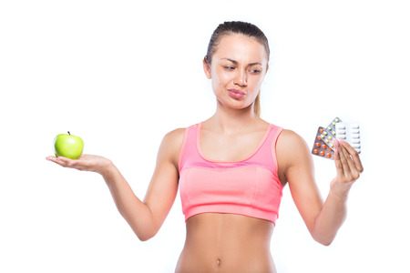 microelements: Fitness woman with pills in one hand, and green apple in another isolated