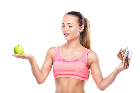 Fitness woman with pills in one hand, and green apple in another isolated. Stock Photo