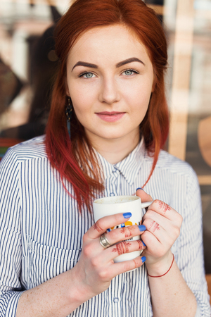 Young Attractive Woman Enjoying A Cup Of Coffee in Cafe.