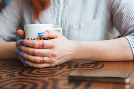 cappaccino: woman hands with coffe on a wood table. Stock Photo