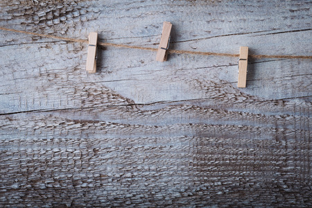 clench: White wooden cloths pin hanging on rope over grunge wood background. Stock Photo