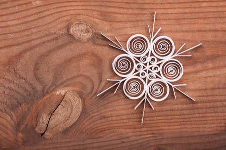Paper snowflake made with quilling technique on a wooden surface.