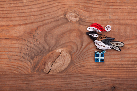 Creative paper bird on a wooden background. Quilling art