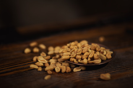 metalic: Peanuts on metalic bowl on wooden background. Stock Photo