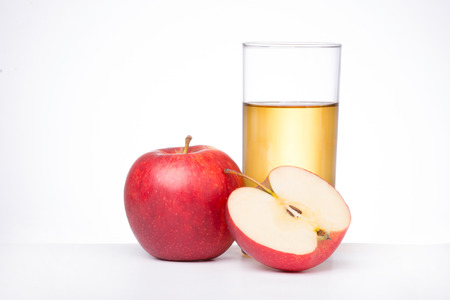 Apples with glass of juice on white background.