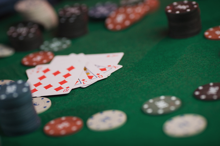 Poker game in mens hands on green table
