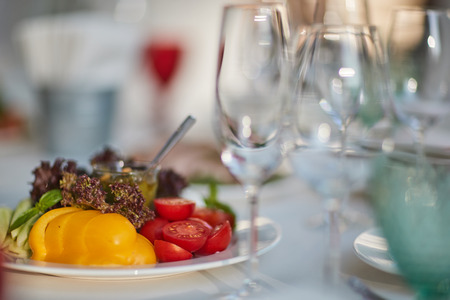 glasses and a plate with vegetables on the table Stock Photo
