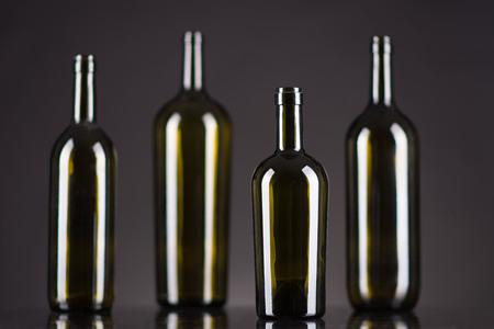 Dark green bottles on a black background