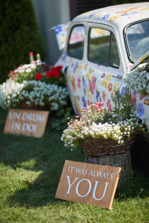 car painted with flowers, surrounded by bouquets of flowers