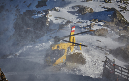 yellow helicopter on the background of snowy mountains