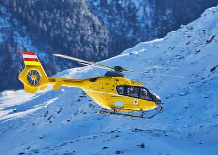 gelber Hubschrauber auf dem Hintergrund der schneebedeckten Berge Standard-Bild