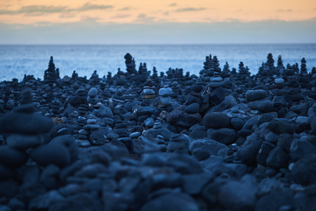 many round stones stacked on top of each other by the ocean
