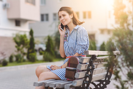 brunette girl speaks by phone and sits on a bench on the street