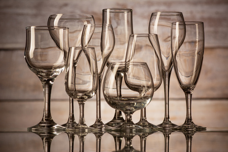 many glasses of different shapes on a wooden background Stock Photo