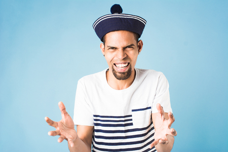 african american guy dressed in sailor uniform on blue background Stock Photo